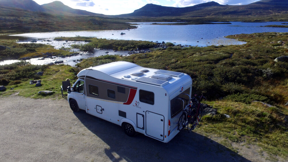 Wohnmobil auf einem Stellplatz direkt vor einem See und mitten in der Natur von Norwegen