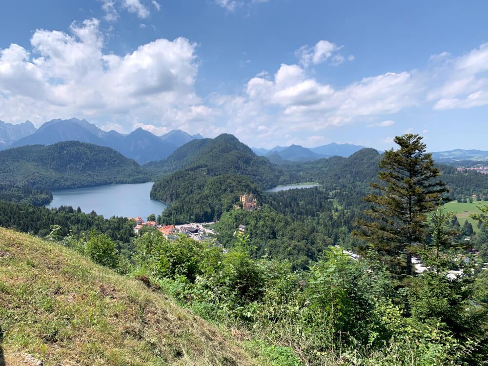 Schloss Hohenschwangau mit einem See und blauem Himmel im Hintergrund auf der Alpenstraße