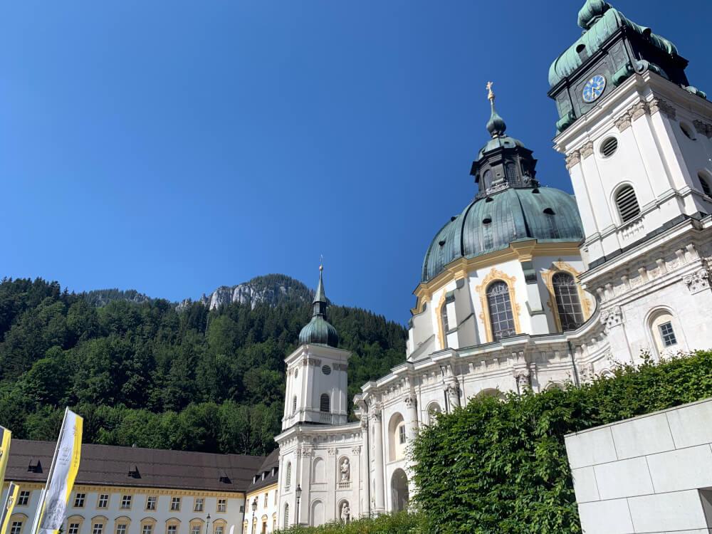 Das Kloster Ettal mit blauem Himmel und Berge im Hintergrund direkt entlang der Alpenstraße