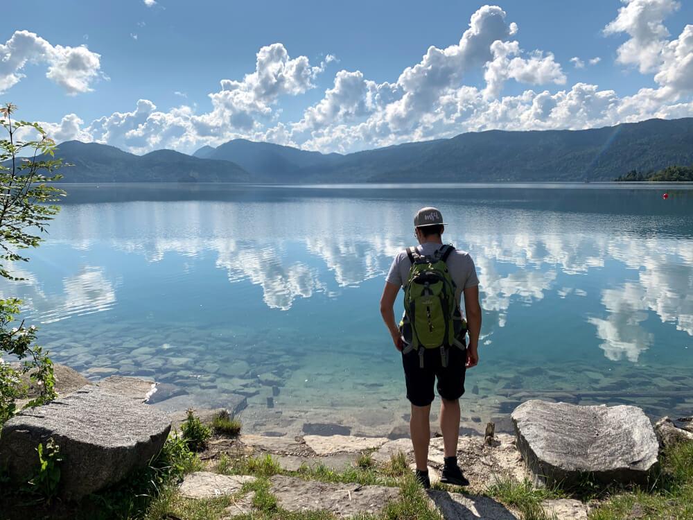 Person im Vordergrund mit dem blauen Walchensee dahinter an der Alpenstraße